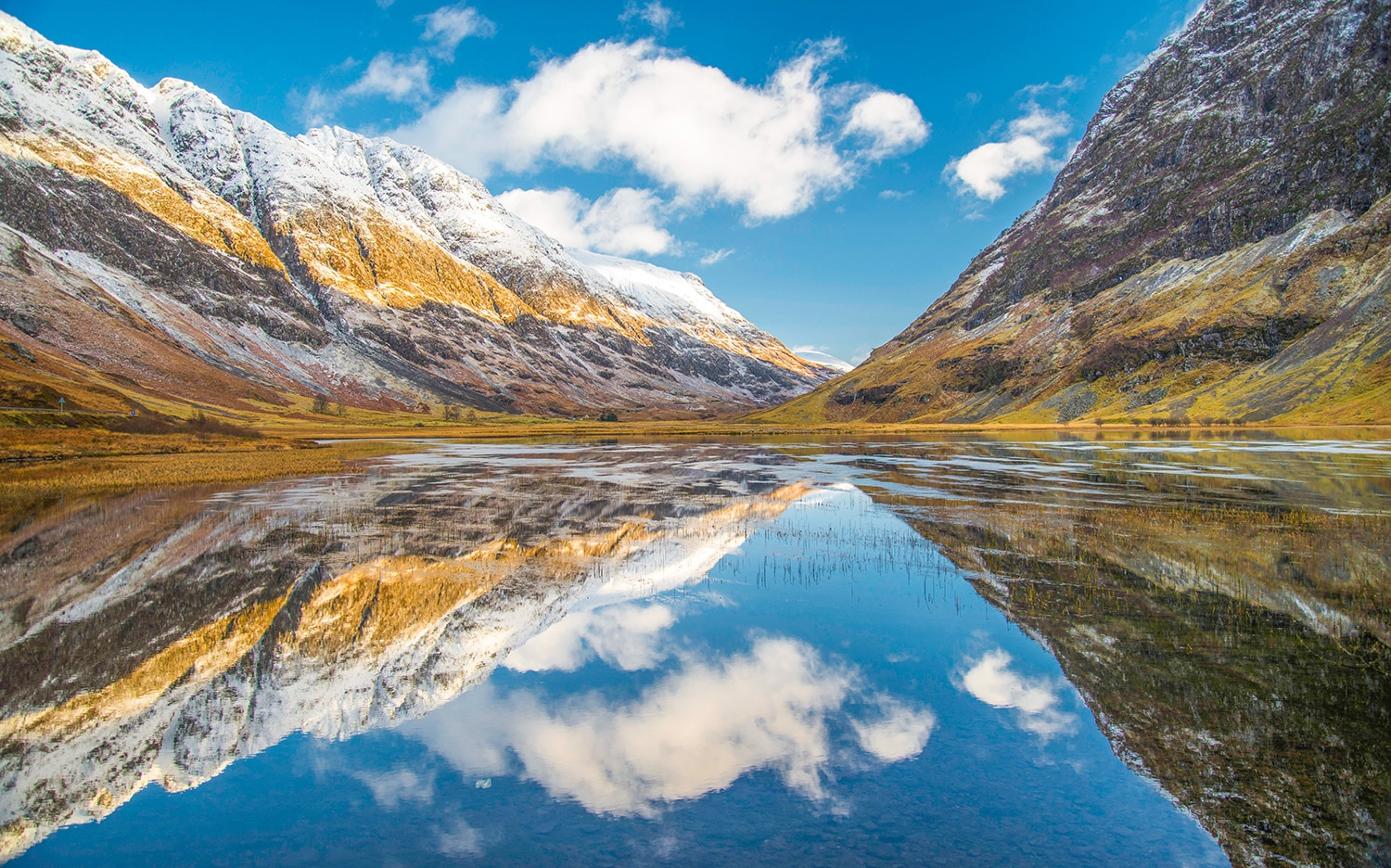 A lovely view of mountains and water in Glencoe, one of the many scenic places to visit on a private tour of Scotland