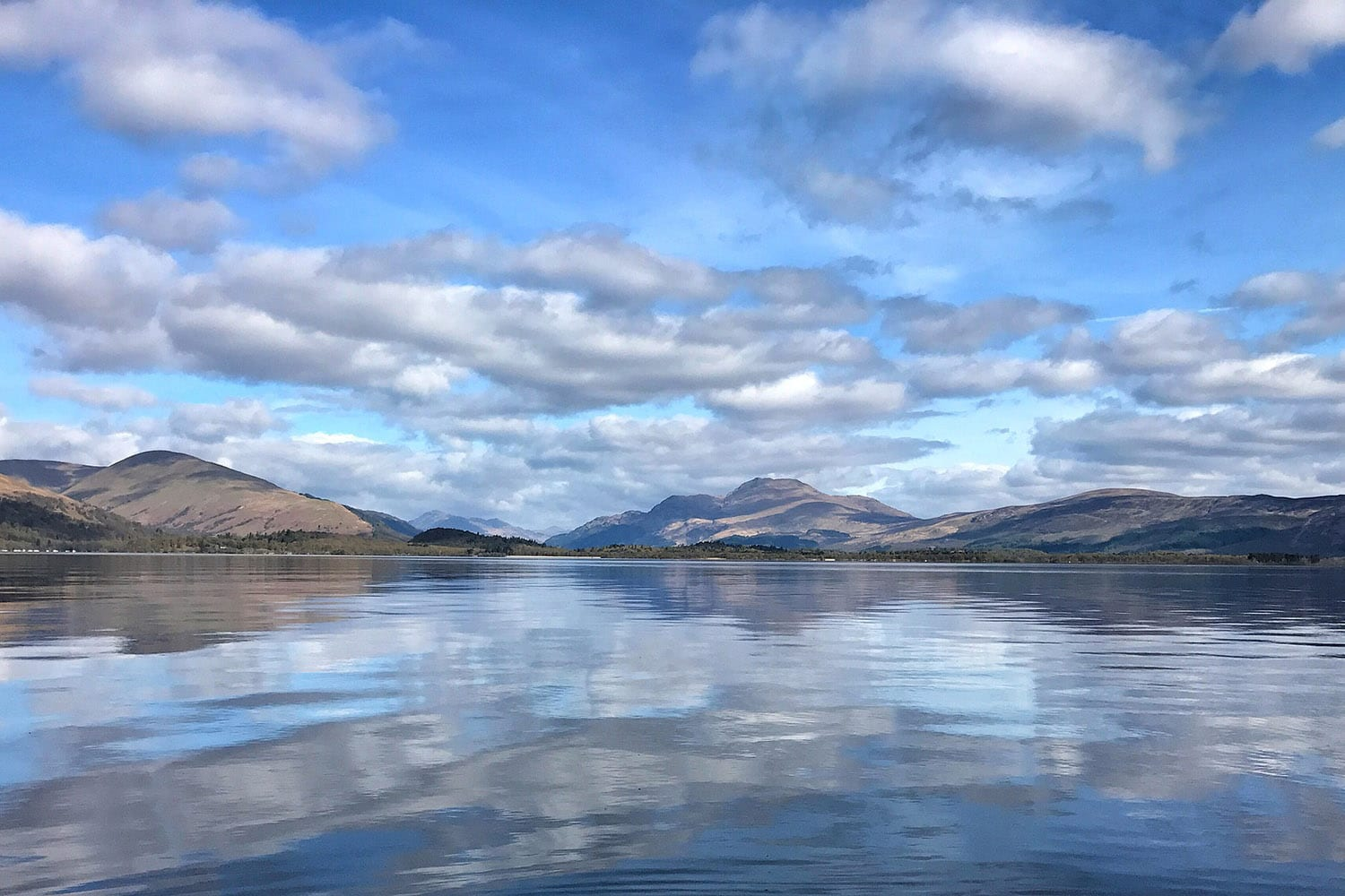 An image of the waters and scenery of Loch Lomond, a highlight of our legends and castles tour of Scotland