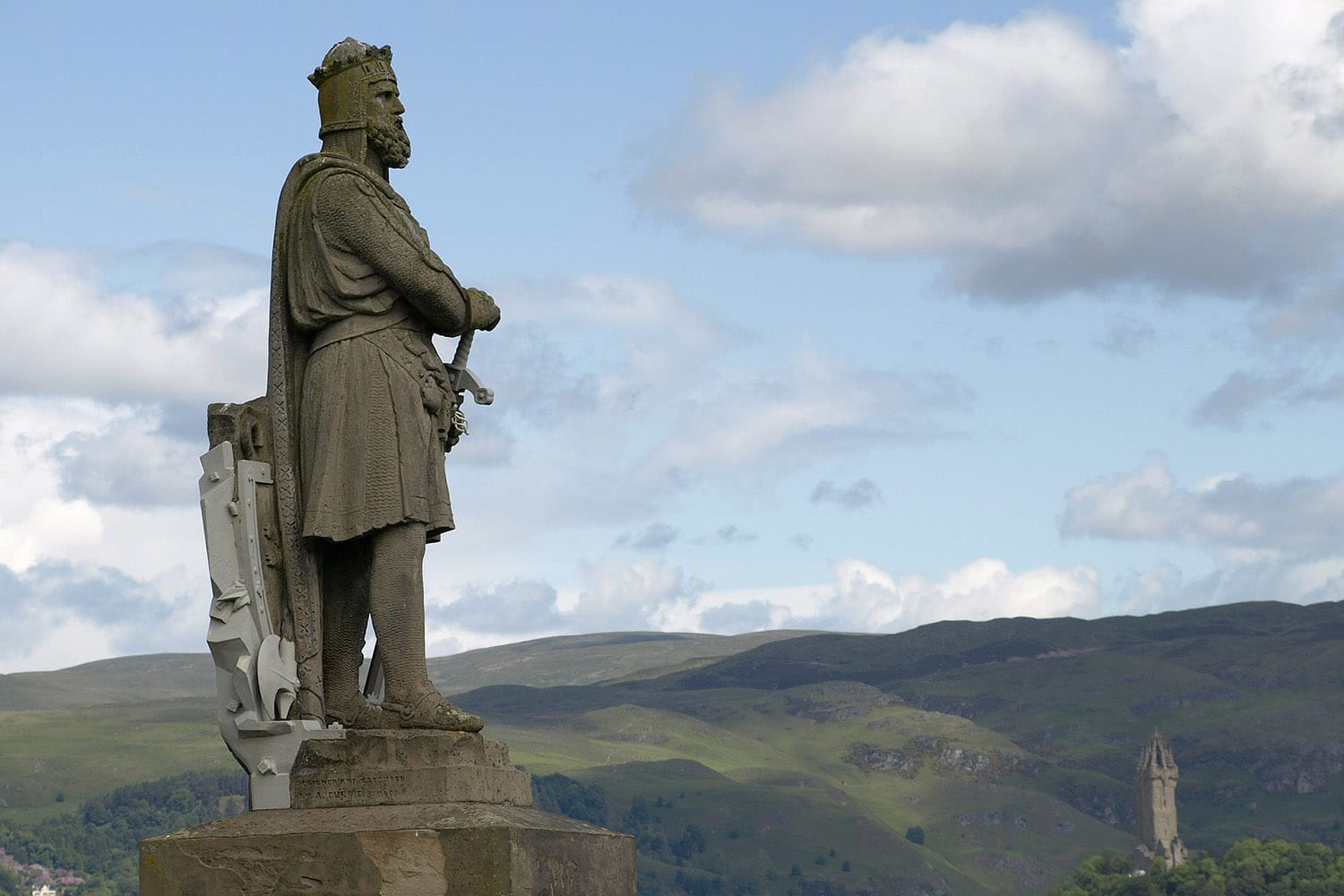 A statue of Robert the Bruce with the Wallace Monument in the background, a highlight of our Outlaw King tour