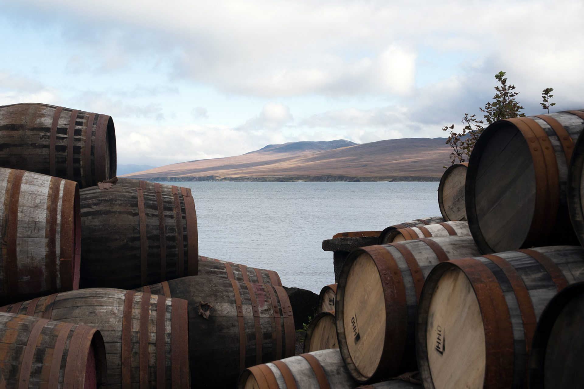 An image of whisky barrels with a scenic view to represent our Scottish Spirit tour, a Scottish whisky tour